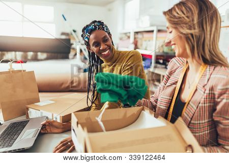 Sales Online. Working Women At Their Store. They Accepting New Orders Online And Packing Merchandise
