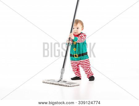 Studio Photo With A White Background Of A Baby Disguised As An Elf Clinging To The Stick Of A Mop