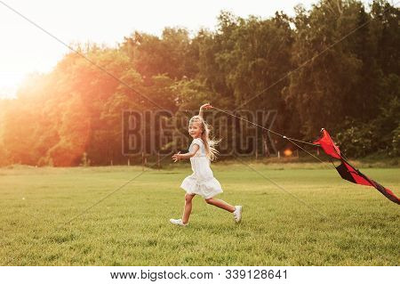 Kite Is Behind Child. Happy Girl In White Clothes Have Fun In The Field. Beautiful Nature.