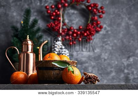Christmas card with tangerines festive decor and firtree on old wooden board in rustic style.