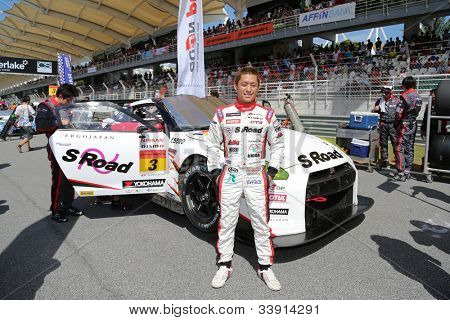 SEPANG - JUNE 10: Driver Katsumasa Chiyo poses with his Nissan GT-R Nismo GT3 car from the NDDP Racing Team at the Autobacs SUPER GT Series Rd 3 on June 10, 2012 at the Sepang Int. Circuit, Malaysia.