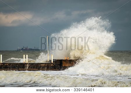 Breakwater And Harbour In Stormy Weather With Huge Waves Crashing Over The Walls Pier. Abnormally St