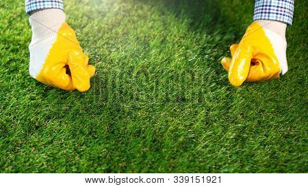Worker Hands On The Synthetic Grass. Artificial Grass Background.