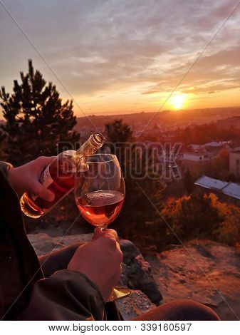 Pouring Wine Outdoor In Front Of The Beautiful Sunset Golden Hour. Wine Bottle With Pink Red White L