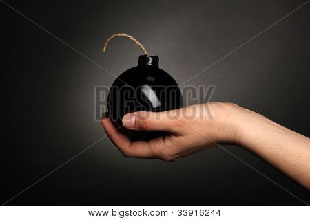Cartoon style bomb in hand on black background