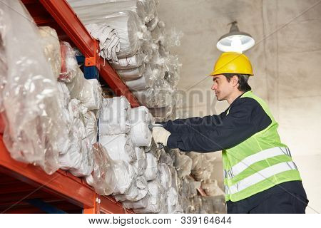 Young worker or specialist warehouse inspects inventory in carpet warehouse