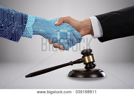 Gavel And Mallet In Front Of Lawyer Shaking Hand With Digital Partners Against Grey Background