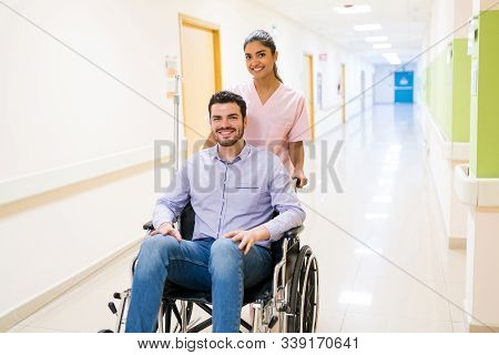 Smiling Orderly Pushing Discharged Mid Adult Patient On Wheelchair At Corridor In Hospital