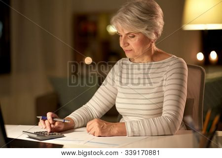 technology, old age and people concept - senior woman with laptop counting on calculator and filling tax form at home in evening