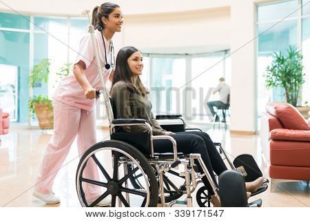 Female Healthcare Worker Pushing Recovered Woman On Wheelchair In Hospital Lobby