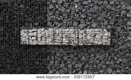 A Stone Wall That Uses Metal And Stone In Harmony. Ecology Friendly Using A Natural Resourses For Co