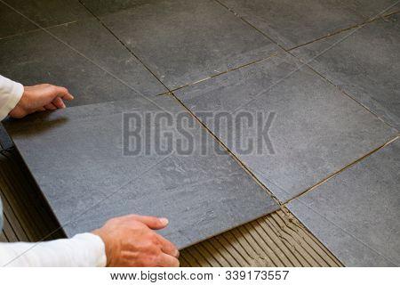 Tiler installing dark ceramic tiles on a floor