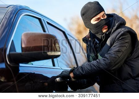Car thief in car theft is at the car door