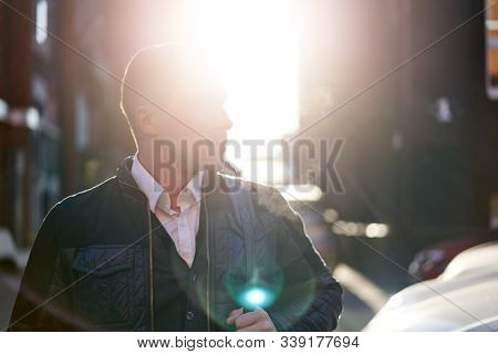 Man looking at side walking in city during day, lensflare effect.