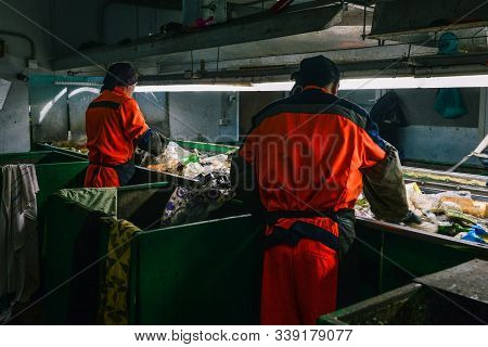Worker At A Waste Processing Plant. A Man Sorts Rubbish With His Hands. Sorting Tape. The Business O