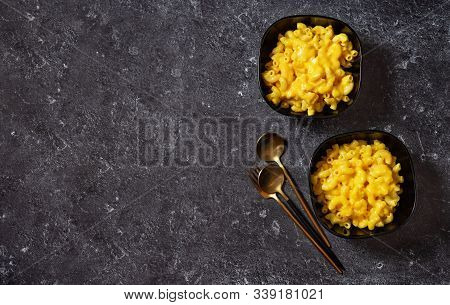 Mac And Cheese Into Two Black Bowls On Dark