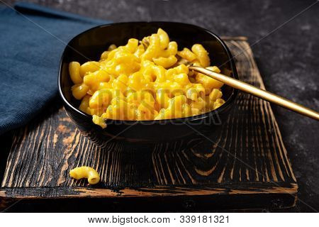Close Up Of Mac And Cheese In Black Bowl On Dark