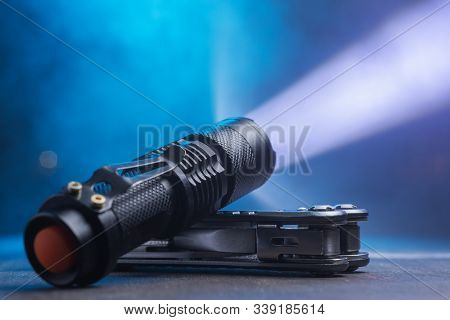 Tactical Waterproof Flashlight. Led Flashlight Shines On The Table In Smoke.