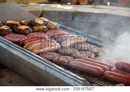 Hot Dogs And Hamburgers Grilling On Bbq.  Also For This Cookout Of Meats Is Sausage And Cheddar Chee