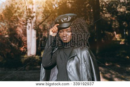 An Outdoor Portrait Of A Cute Young Curly-hair African Female In A Leather Jacket, Peaked Cap, Black