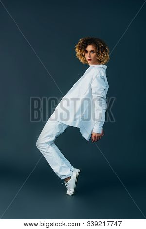 Side View Of Curly Teenager In Total White Outfit Posing On Tiptoe Isolated On Green