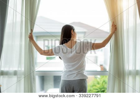 Rear View Of Asian Woman Waking Up In Her Bed Fully Rested Opening Window Curtains And Looking Throu