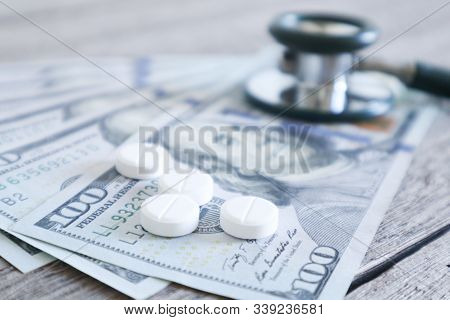 Medicine Pill And Medical Stethoscope On 100 Dollar Banknote Background.healthcare Insurance And Med