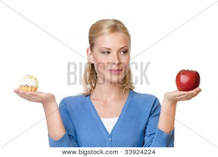Pretty woman makes a tough choice between cake and apple, isolated on white