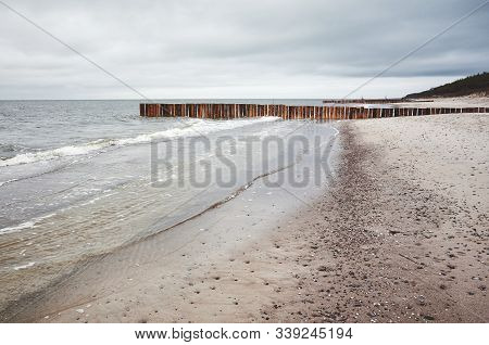 Empty Beach On A Cloudy Day With Wooden Groin In Distance.