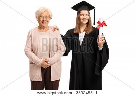 Female graduate with bachelor degree in a graduation gown posing with her grandmother isolated on white background