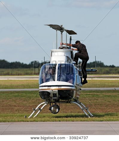 Pilot checking police helicopter before taking flight poster