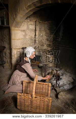 Renaissance portrait in Rembrandt style of a young woman in medieval peasant costume working near the authentic fireplace