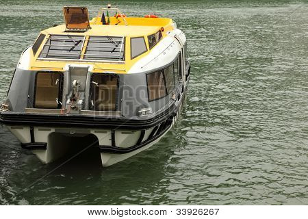 Small empty lifeboat with roof and windows floats at reservoir