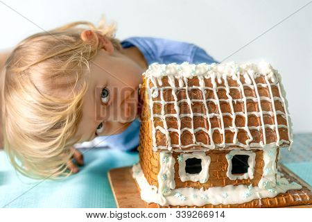 Сute Little Boy Eats Gingerbread House And Having Fun. Kid Enjoy Christmas Traditions. Child Broke A