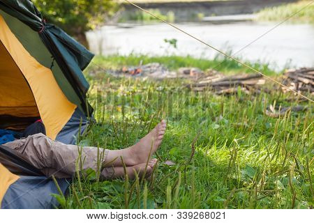 Camper Lying In A Tent Near The River. Campers Legs (feet) Sticking Out Of The Tent.