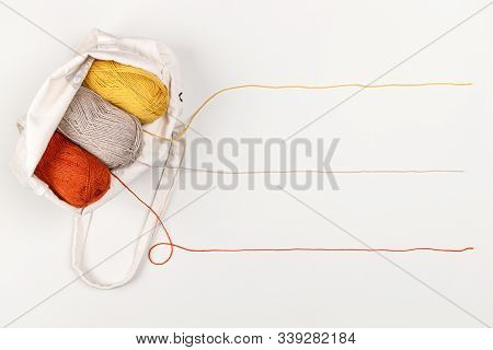 Yellow, Red And Beige Clews Of Yarn In A Textile Bag. Strings Of Yarn Form A Line For The Text. Copy