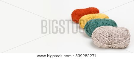 Beige, Green, Yellow And Red Clews Of Yarn Of Pastel Colors Lie One Behind The Other. Selective Focu