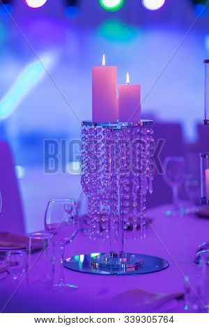 Festive Table Decorated With Composition Of Candles And Silver Candlesticks In Colored Light In The