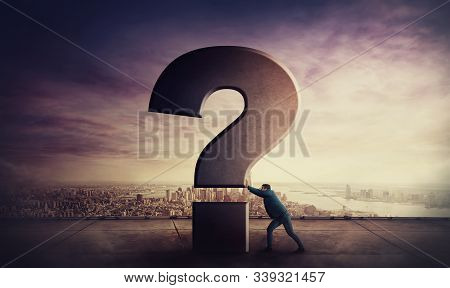 Puzzled Businessman On The Rooftop Pushing A Huge Interrogation Mark. Business Questions Concept, Ma
