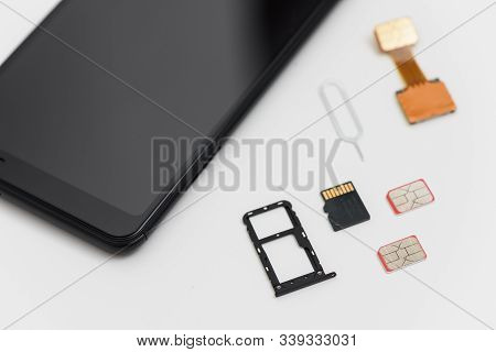 There Are Sim Cards, A Memory Card, A Pin Near The Smartphone. The Device Has An Open Slot.
