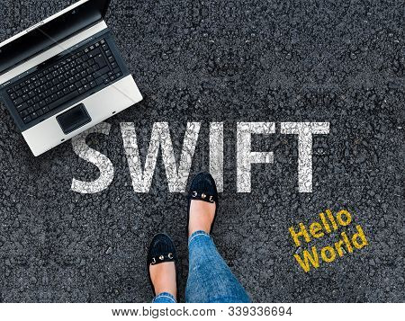 Swift Programming Language. A Woman Steps To A Laptop And Word Swift On Asphalt.