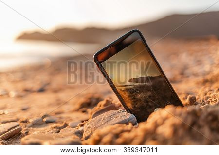 The Concept Of The Photos On The Phone. The Smartphone Lies Buried In The Sand On The Beach, And Tak