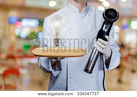 Concept Of The Idea Of The Sous Vide Cooking. The Chef Shows A Burning Light Bulb And Cook Sous Vide