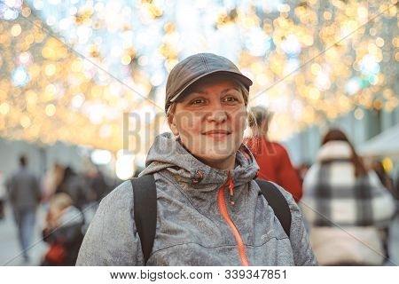 An Elderly Woman On The Background Of Christmas Lights On A Festive Street