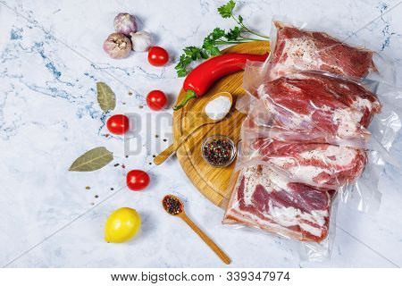 The Seasoning And Meat Is Vacuum Packed On A White Background .