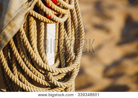 Rope On Boats Deck. Hanging Rope Wool Close-up On Blurred Background. Marine Rope. Ship Rope