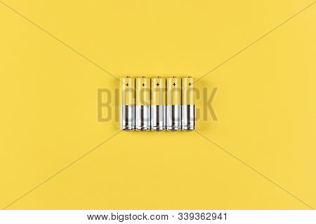 Photo Of Five Gray-yellow Alkaline Aa Batteries On A Yellow Background. Recycling Of Rechargeable Ni