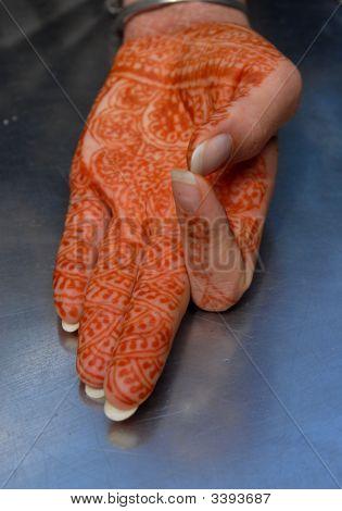 Mehandi girl's hand covered in henna tattoo