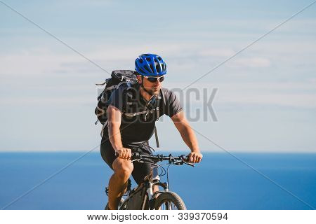 Young Guy Riding A Mountain Bike On A Bicycle Route In Spain. Athlete On A Mountain Bike Rides Off-r