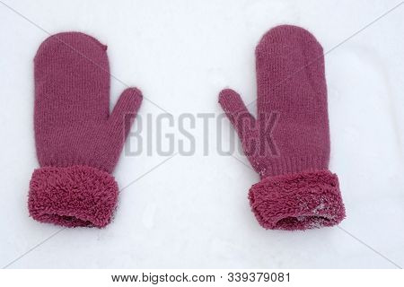 Warm Female Winter Mittens. Two Mittens Of Lilac Color Lie On White Snow, Top View. Mittens On Four